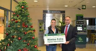 Rafael D. Rodríguez, de Cajasiete, entrega la Nómina Extra a Raquel Pérez en la sede de la entidad.